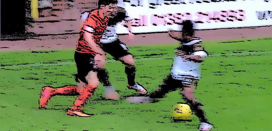Blair Spittal dribbling past two defenders
